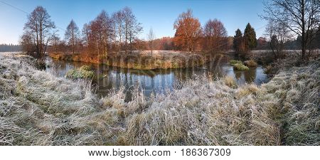 Beautiful autumn morning panorama with frosty grass, small river, falling trees and blue sky.Cold autumn morning.Beautiful autumn morning panorama with frosty grass, small river, falling trees and blue sky.Autumn morning landscape with the first frost, th