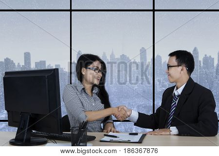 Young businessman shaking hands on his new employee while sitting in the office with winter background on the window