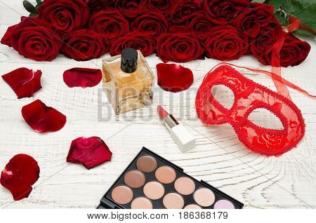 Red carnival mask perfume and lipstick on a wooden table on a background of scarlet roses