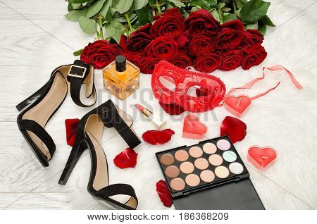 Red carnival mask perfume shoes and lipstick on a wooden table on a background of scarlet roses