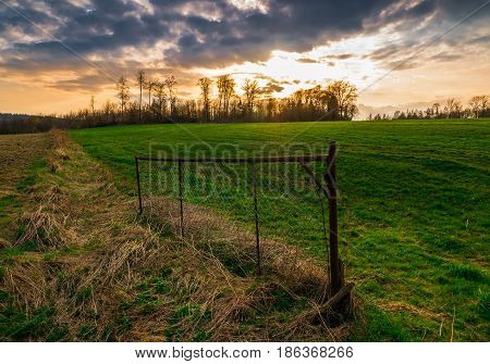 The Old And Rusty Wire Fence In A Field At Sundown