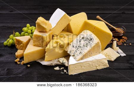 Various types of cheese on black wooden table background. Cheddar, parmesan, emmental, blu cheese.