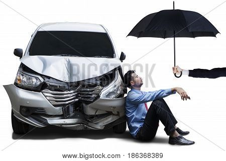 Tired businessman sitting under umbrella next to a dented car isolated on white background