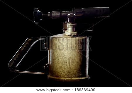 Old petrol blowtorch on a black background
