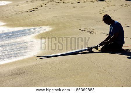 Surfer sitting on beach sand at Ipanema beach