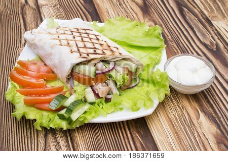 Shawarmas on lettuce isolated on a wooden background