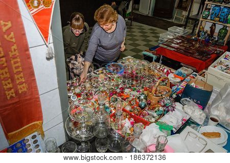 Moscow, Russia - March 19, 2017: Two female customers at the counter with vintage glass Christmas-tree toys at the fair of antique hobby and collectors items