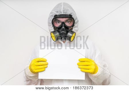 Man In Coveralls With Gas Mask Is Holding Blank White Paper