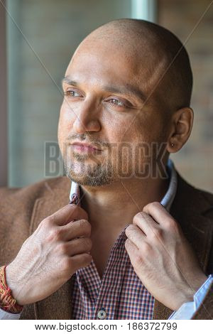 Closeup headshot portrait of stylish handsome indian man, strong and confident, holding his shirt collar