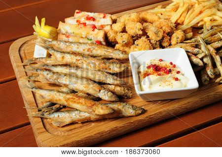 big wooden board with fried fush, mussels, french fries served as companion for beer or other alcool drinks