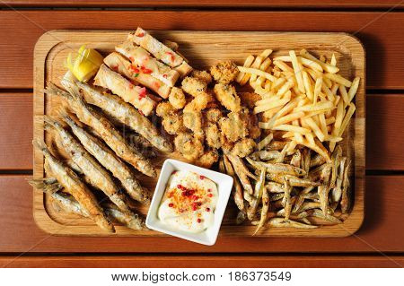 big wooden board with fried fush, mussels, french fries served as companion for beer or other alcool drinks, top view
