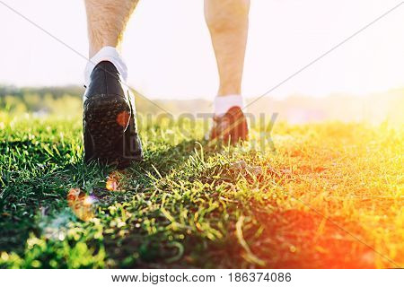 Runner man feet running in park closeup on shoe. Male fitness athlete jogger workout in wellness concept at sunset. Sports healthy lifestyle concept.