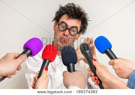 Reporters with microphones making interview with funny scientist - journalism and broadcasting concept
