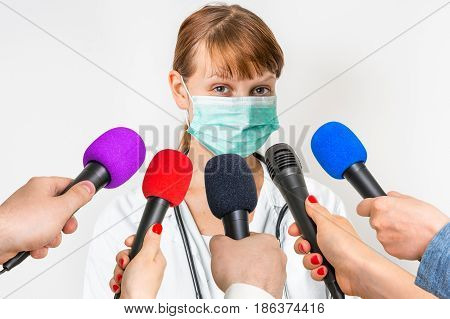 Reporters with microphones making interview with female doctor - journalism and broadcasting concept