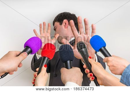 Reporters with microphones making interview with young businessman - journalism and broadcasting concept