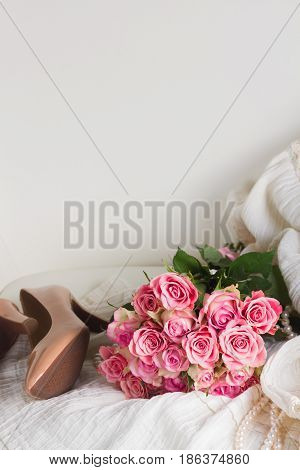 Female dress and jewellery with fresh rose flowers bouquet and hight heel shoes on chair with copy space