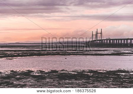 Second Severn crossing a bridge linking Bristol to Wales. Panoramic view at sunset with low tide on the river. Travel and nature concepts