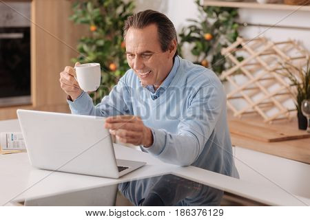 Enjoying modern technologies. Positive delighted old man sitting in the kitchen while enjoying cup of coffee and using laptop