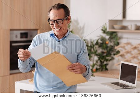 Enjoying my everyday post. Energetic upbeat elderly businessman sitting at home while enjoying morning routine and getting letter from envelope