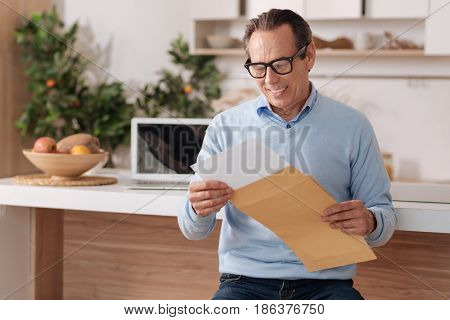 Checking my business post. Smiling lively aged businessman sitting at home while enjoying morning routine and getting documents from envelope