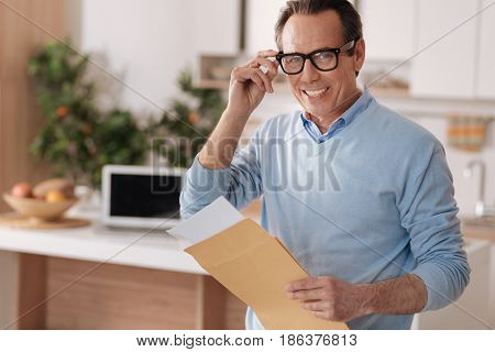 Enjoying my comfortable workplace. Smiling charming aged freelancer sitting at home while enjoying morning routine and becoming familiar with documents from envelope