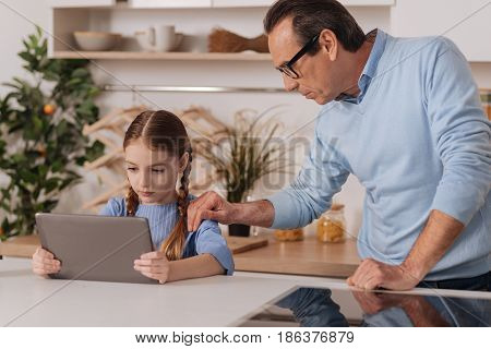 Preventing you from addiction. Loving caring aging grandfather standing at home while expressing care and taking away tablet from little granddaughter