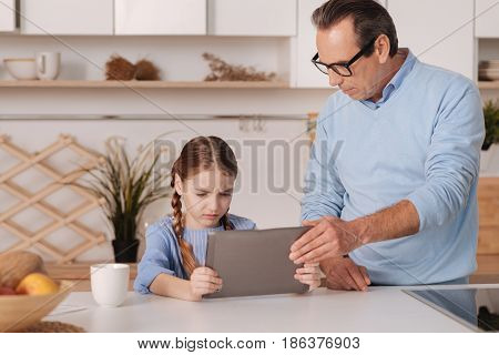 Stop playing stupid games. Strict old retired grandfather standing at home while taking away tablet from granddaughter and upbringing little kid
