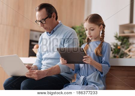 Addicted to innovative technologies. Aged motionless retired man sitting indoors and using gadgets with granddaughter while surfing the Internet and checking social media profiles