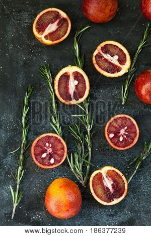 Red Sicilian Orange Whole And Cut On A Dark Background With Branches Of Rosemary. Daylight, Open Spa