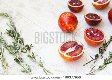 Red Sicilian Orange Whole And Cut On A Light Background With Branches Of Rosemary. Daylight, Open Sp