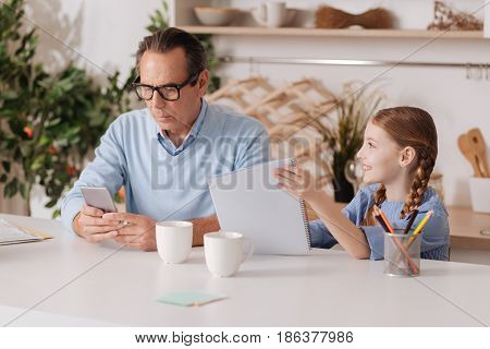 Always busy. Aged busy concentrated grandfather using smartphone at home and ignoring granddaughter while working and texting sms
