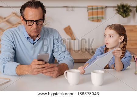 Chained in virtual world. Involved busy aging businessman using gadget at home and ignoring child while working and surfing Internet