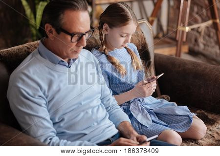 Involved in my own world. Retired indifferent addicted man sitting on the couch and using mobiles with kid while surfing the Internet
