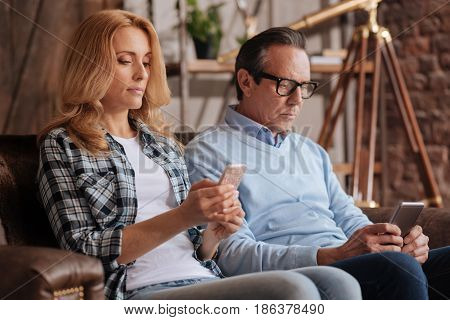 Ruined private life. Involved mature captured couple sitting on the couch at home and using mobiles while surfing the Internet and expressing apathy