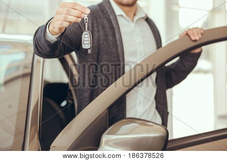 Young man in a car rental service holding keys