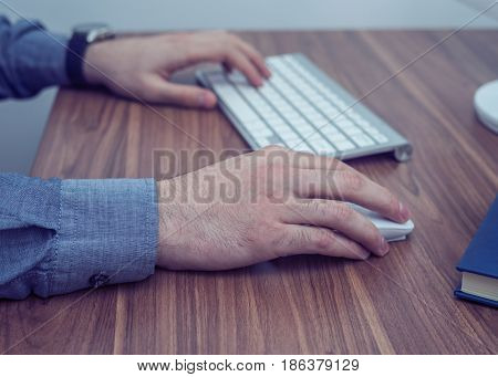 Hands working with wireless keyboard and mouse on wooden table. Office concept