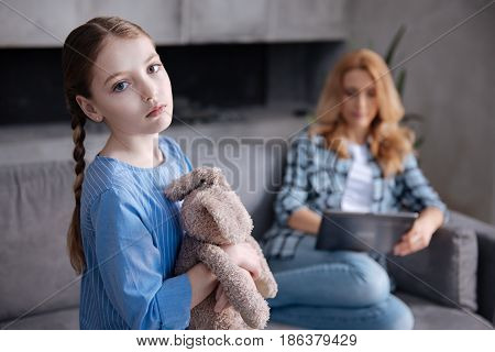 Oppressive atmosphere. Cute lonely disappointed girl waiting for parent love at home and hugging fluffy toy while mother surfing Internet in the background