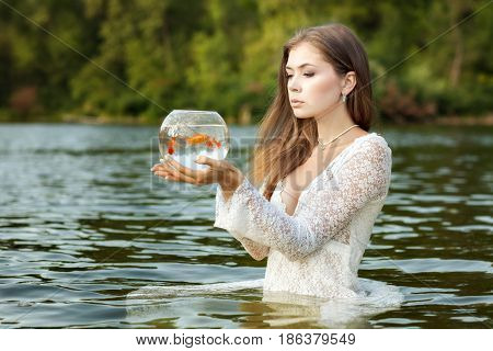 Woman stands in the water in her hands an aquarium with goldfish she makes her wishes come true.