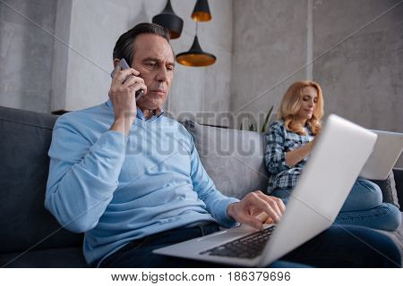 Career first of all in my life. Serious aging involved man sitting at home and using modern gadgets with wife while surfing the Internet and having business conversation