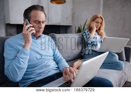 Without time for private life . Confident charismatic aged man sitting at home and using modern devices with wife while surfing the Internet and having business conversation
