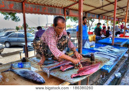 Bandar Abbas Hormozgan Province Iran - 16 april 2017: The seller of fish in the outdoors fish market squatting under a canopy and cuts fresh tuna