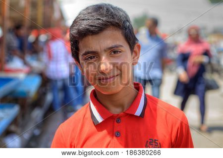 Bandar Abbas Hormozgan Province Iran - 16 april 2017: One unknown Persian youth about 14 years old in an orange shirt a close-up portrait against a city street background.
