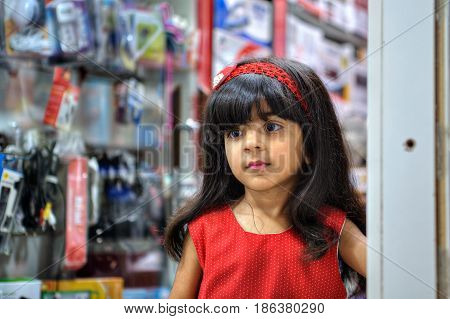 Bandar Abbas Hormozgan Province Iran - 16 april 2017: One unknown little Persian girl in a red dress standing at the entrance to the electronics store a close-up portrait only for editorial use.