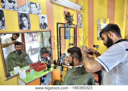 Bandar Abbas Hormozgan Province Iran - 16 april 2017: Iranian Barber salon Persian hairdresser makes the hair style for man.