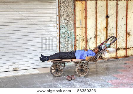 Bandar Abbas Hormozgan Province Iran - 16 april 2017: One unknown male loader sleeps in a hand trolley only for editorial use.