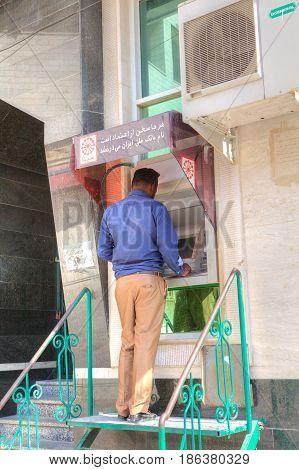 Bandar Abbas Hormozgan Province Iran - 16 april 2017: One man uses a street ATM to withdraw cash.