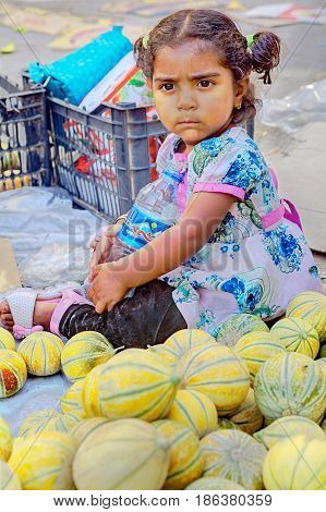 Bandar Abbas Hormozgan Province Iran - 16 april 2017: One unknown little girl about three years old sits outside the eastern bazaar on the sidewalk near the melons just editorial use.