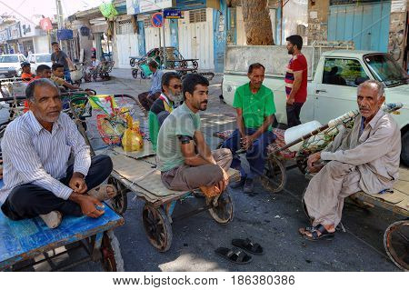 Bandar Abbas Hormozgan Province Iran - 16 april 2017: Several workers of the bazaar are sitting on the platforms of hand carts during a break in work.