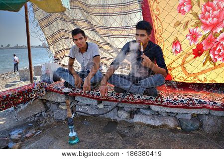 Bandar Abbas Hormozgan Province Iran - 16 april 2017: Two young men rest in the shade under the cloth canopy on the shore of the Persian Gulf and smoke a hookah.