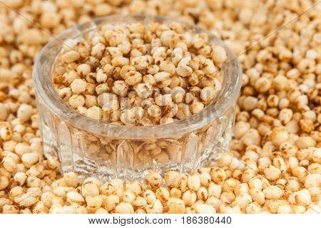 Puffed quinoa seeds into a small glass container (Chenopodium quinoa)